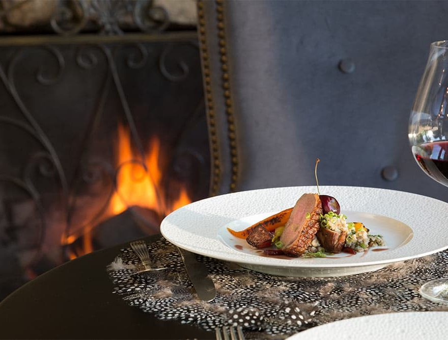 Duck with glass of Red wine and fireplace in background