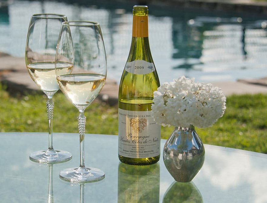 Vintage 2009 Wine by the pool, with two wine glasses, and small flowers
